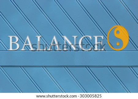 Balance written on a wooden blue background with a yin yang symbol.