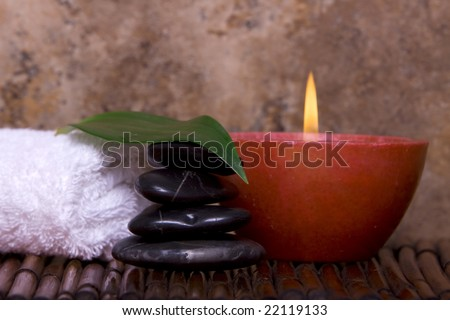 Balanced pebble rocks, candle, white towel set on bamboo for spa treatment