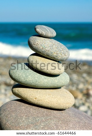 balanced pebbles on sea in nice summer day - stock photo