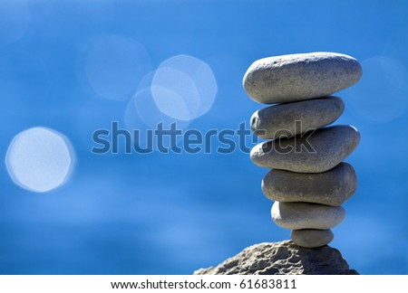 Balanced pebbles stack over blue sea - stock photo