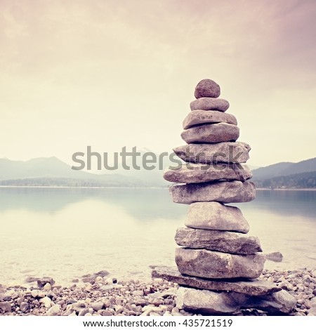 Balanced stone pyramide on shore of blue water of mountain lake. Blue mountains in water level mirror. Children built pyramid from pebbles.  Poor lighting conditions. - stock photo