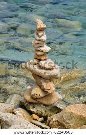 Balanced stone structure on rocky shore. Rock pile by the sea water. - stock photo