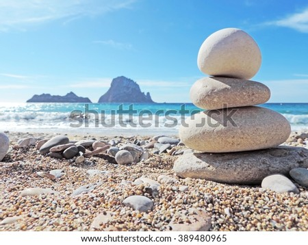 Balanced stones on the beach of Cala d'Hort, Ibiza Island. View to the magic rock es Vedra in the background  - stock photo