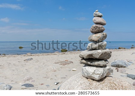 Balanced stones stacked to a tower on the beach of the Baltic Sea against blue sky with copy space - stock photo
