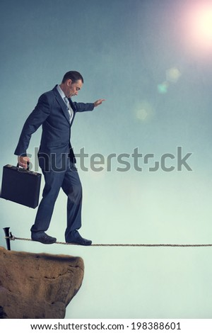 balancing businessman starting out on a tightrope
