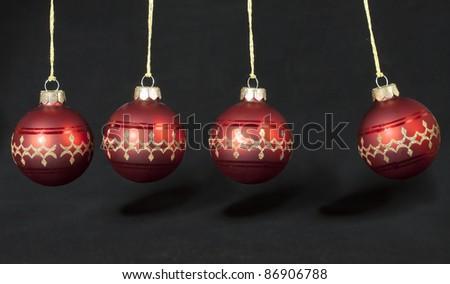 Balancing Christmas balls on black - stock photo