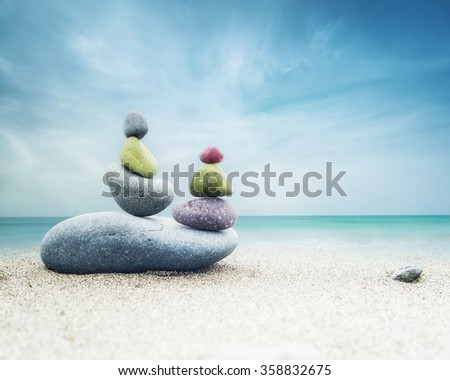 Balancing colorful zen stones pyramid on sandy beach under blue sky. Beautiful nature and spiritual concept - stock photo