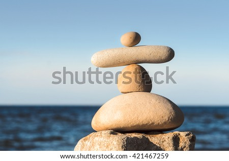 Balancing of pebbles on sea background - stock photo