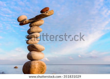 Balancing of pebbles on sky background - stock photo