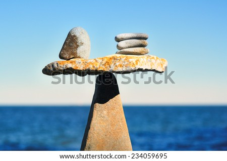 Balancing of pebbles on the top of triangle stone - stock photo
