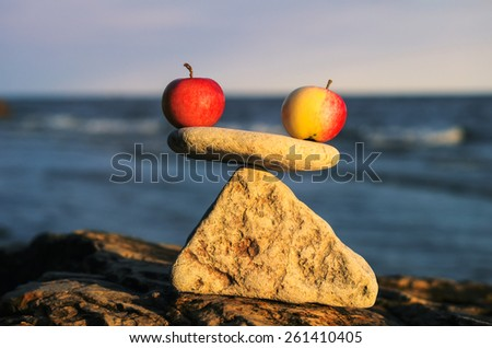 Balancing of two apples on the top of stone - stock photo