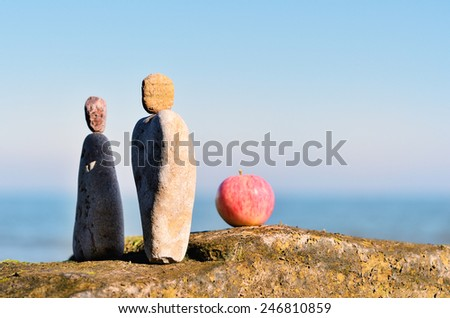 Balancing of two triangle stones and apple on the seacoast - stock photo