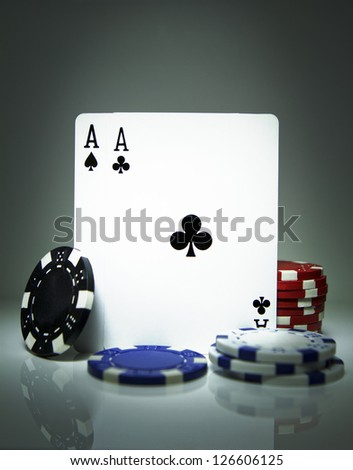 Balancing pair of Aces playing cards surrounded by poker chips. Gambling concept - stock photo