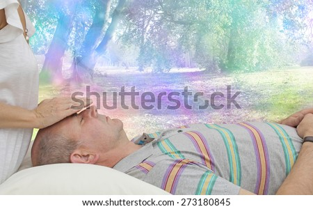 Balancing Third Eye Chakra - Healing practitioner sensing energy of male client lying supine on couch with a colorful fantasy rainbow bokeh background - stock photo