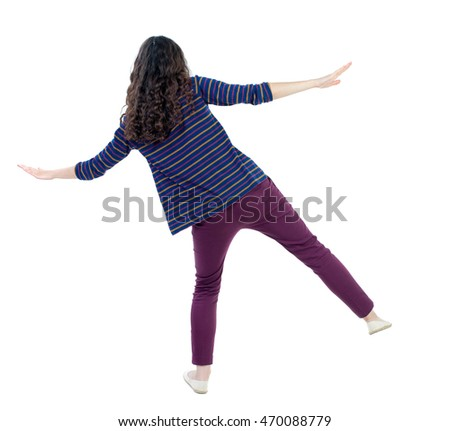 Balancing young woman.  or dodge falling woman. Rear view people collection.  backside view of person.  Isolated over white background. Long-haired curly girl in a blue striped sweater balances on one