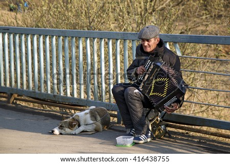 BALASHIKHA, RUSSIA - APRIL, 13. Street musician playing the accordion, with the dog on the bridge on April 13, 2014 in city Balashikha, Moscow region.   - stock photo