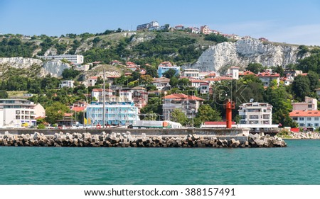 Balchik resort town. Entrance to the port, red lighthouse on the pier. Coast of the Black Sea, Varna region, Bulgaria