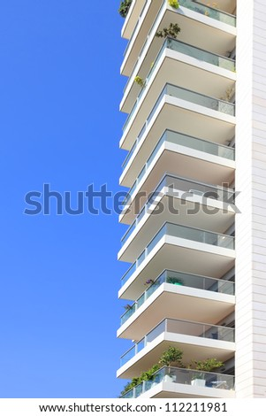 Balconies of modern building on the blue sky background - stock photo