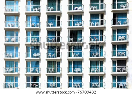 Balconies of modern hotel with white empty beach chaise - stock photo