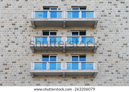 Balconies with blue glass fence at stone building