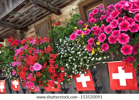 Balcony and flags on chalet in Swiss Alps, Switzerland - stock photo
