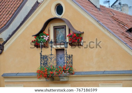Balcony in the city of Prague decorated with flowers and an ancient tile painting