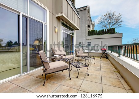 Balcony, large terrace with furniture in new apartment building. - stock photo