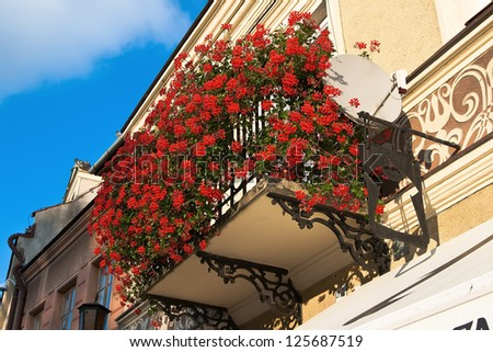 Balcony on the second floor of an old house in the colors of red geraniums - stock photo