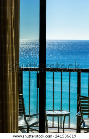 Balcony overlooking Gulf of Mexico in Destin, Florida through sliding glass door. - stock photo