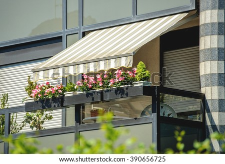Balcony with awning opened and beautiful flowers - covered by sun-shield on a warm summer day - stock photo