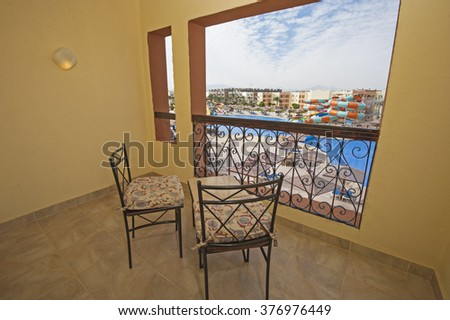 Balcony with chairs and table overlooking swimming pool at luxury tropical hotel resort - stock photo
