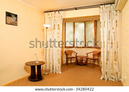 Balcony with chairs and table. Photo in the frame made by the author