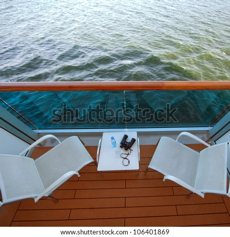 balcony with chairs table bottle glass binoculars on ship , view from above - stock photo