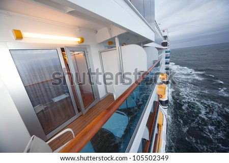 balcony with chairs table lamp on ship with view on sea in evening - stock photo