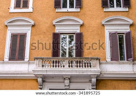 Balcony with columns and windows with shutters with marble ornaments in the old vintage house in Rome, capital of Italy