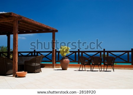 Balcony with 3 rattan chairs and ocean at the background - stock photo