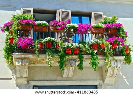 Balcony with vibrant multicolored petunias. - stock photo