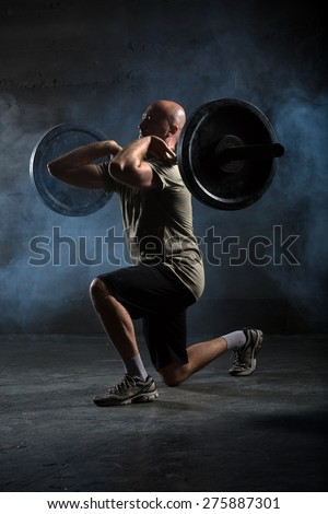 Bald athlete doing exercise with a barbell. Studio shot. - stock photo