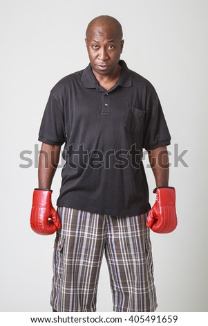 bald black men in his forty, wearing polo and short, with red boxing gloves - stock photo