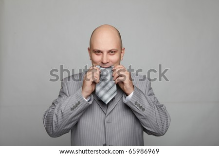 Bald businessman in a gray suit with a gray background eats his own tie. Funny business