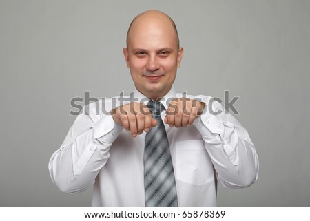 Bald businessman in a gray suit with a gray background makes various hand gestures