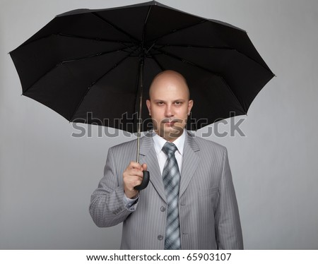 Bald businessman in a gray suit with a gray background with a black umbrella in hand