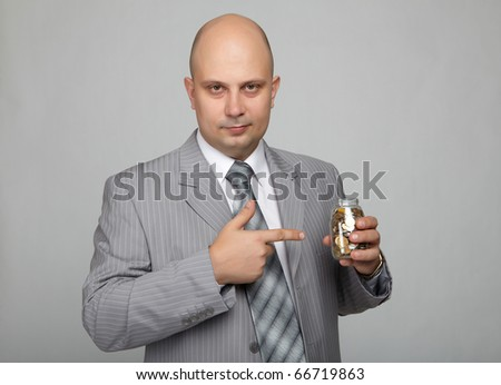 Bald businessman in a gray suit with a gray background with a can with coins in hand