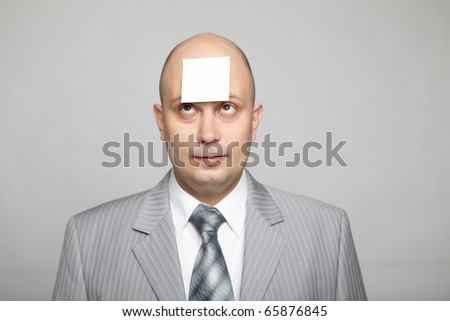 Bald businessman in a gray suit with a gray background with a sticker on his forehead. Funny business