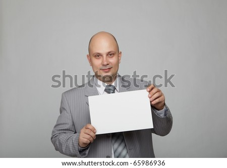 Bald businessman in a gray suit with a gray background with a white square in the hands of