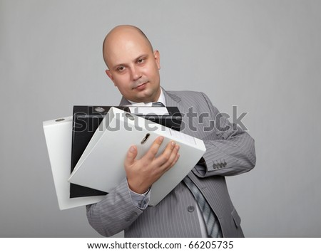 Bald businessman in a gray suit with a gray background with folders for papers in their hands