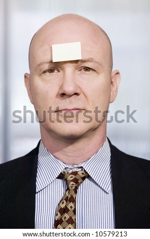 Bald businessman in with a blank sticky note on his forehead - stock photo