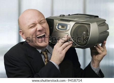 Bald businessman listening to a boom box - stock photo
