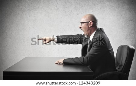 Bald businessman pointing his index finger at someone - stock photo