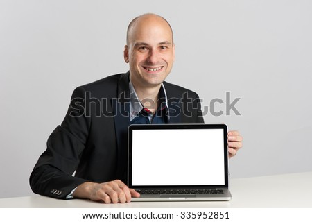 bald businessman sits at the desk showing laptop with copy space - stock photo